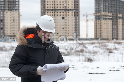 istock Worker or engineer holding drawing in hands and reading it on background of new apartment buildings and construction cranes on background.Architect engineer concept. Soft focus. 926715956