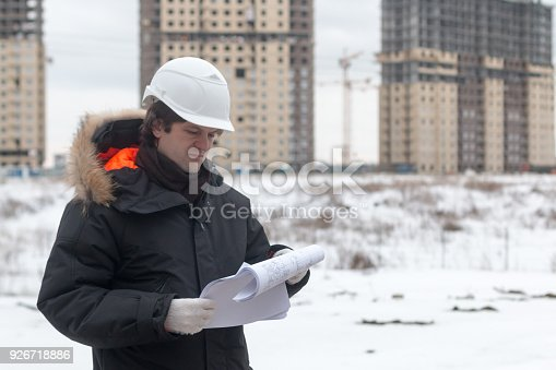 istock Worker or engineer holding drawing in hands and reading it on background of new apartment buildings and construction cranes on background. Architect engineer concept. Soft focus. 926718886