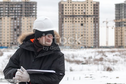 istock Worker or engineer holding drawing in hands and reading it on background of new apartment buildings and construction cranes on background. Architect engineer concept. Soft focus. 932270814