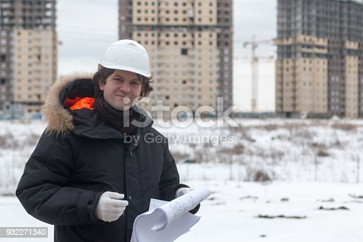 istock Worker or engineer holding drawing in hands and reading it on background of new apartment buildings and construction cranes on background. Architect engineer concept. Soft focus. 932271340
