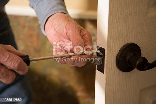 Worker in blue uniform or homeowner installing or repairing door knob on an interior door in the home.
