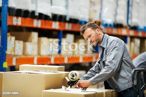 Male worker packing cardboard box at distribution warehouse
