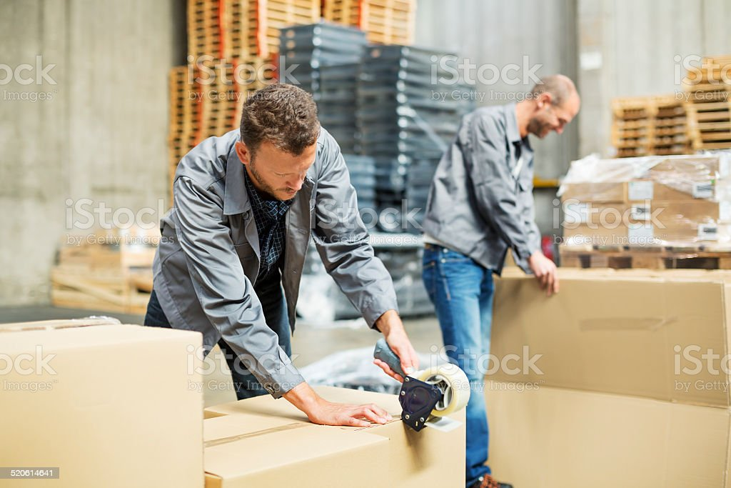 Worker packing cardboard boxes in warehouse stock photo