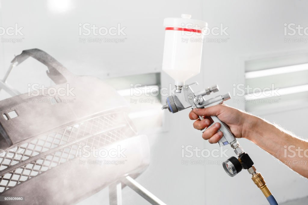 worker painting a car black blank parts in special garage, wearing costume and protective gear stock photo
