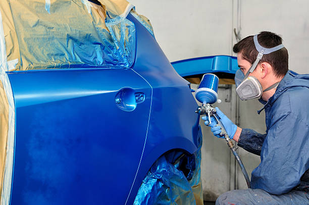 worker painting a car. - auto body repair stock photos and pictures