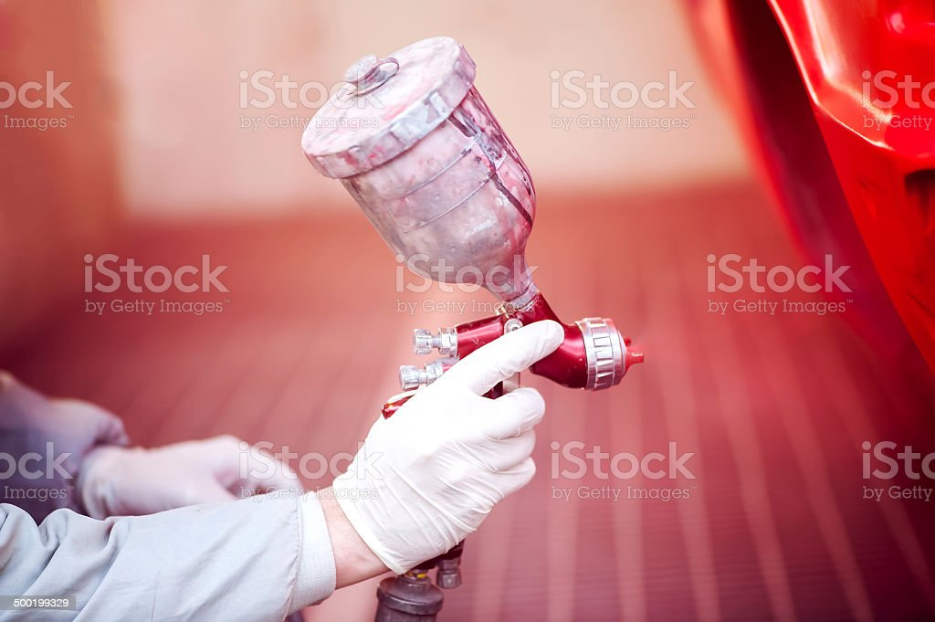 Worker painting a red car in paiting booth stock photo