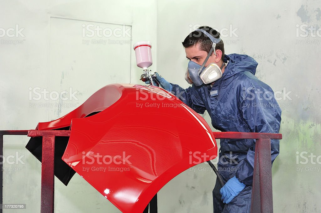 Worker painting a red panel. royalty-free stock photo