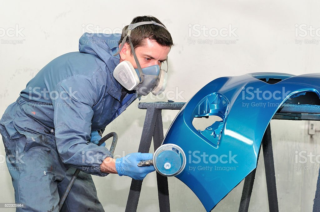 Worker painting blue bumper. stock photo