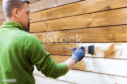istock worker painting house exterior with brown wood protective color 855082622