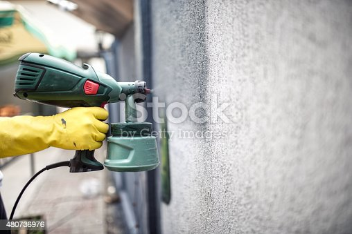 istock Worker painting wall with grey paint using professional spray gun 480736976