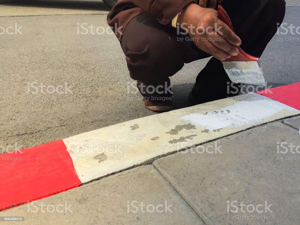 Worker painting White and red  line on the street stock photo