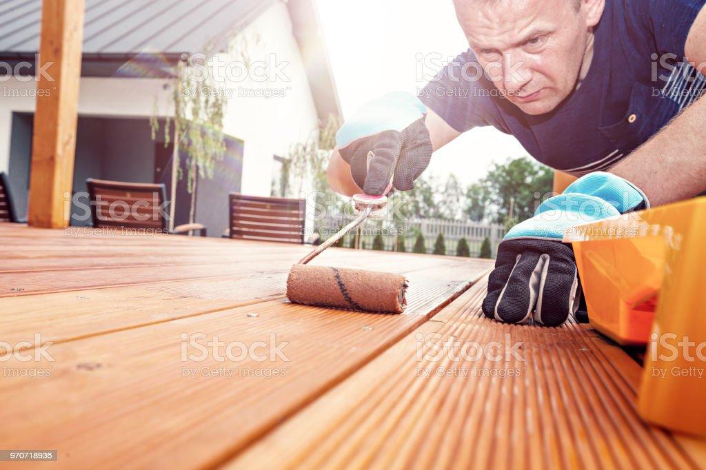 Arbeiter malt die Bretter auf der Terrasse mit einem Farbroller – Foto