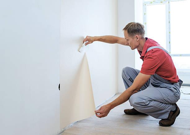 worker pasting wallpapers. - französisches haus dekor stock-fotos und bilder