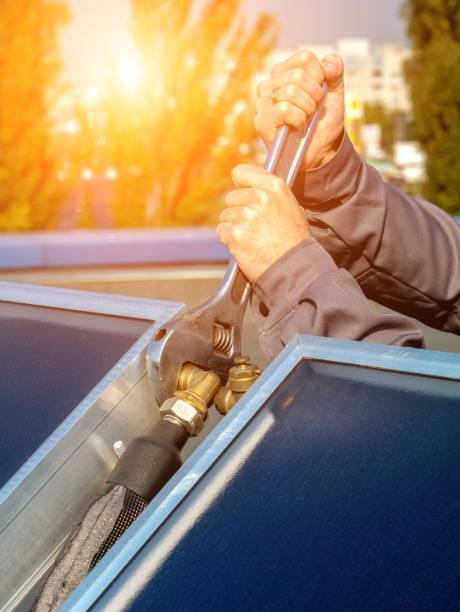 Trabalhador executa a instalação de painéis solares - foto de acervo