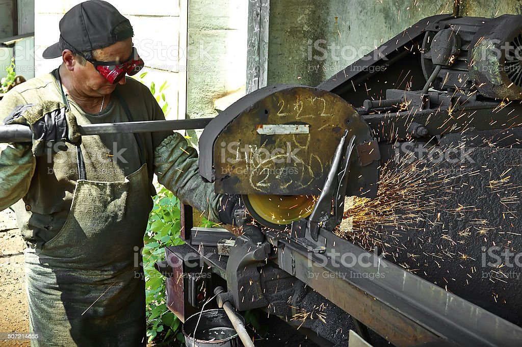 Worker performs work on metal, sparks stock photo