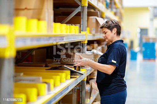 istock Worker picking inventory in warehouse 1182598775