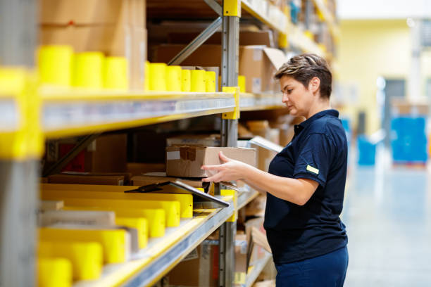 Worker picking inventory in warehouse stock photo