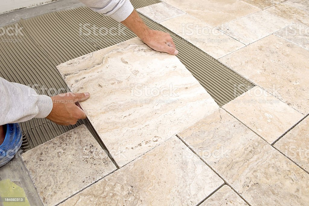 Worker Places New Marble Tile on a Bathroom Floor stock photo