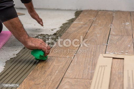 istock Worker placing ceramic floor tiles on adhesive surface, leveling with rubber hammer. 1090948274