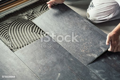 istock Worker placing ceramic floor tiles 979339958