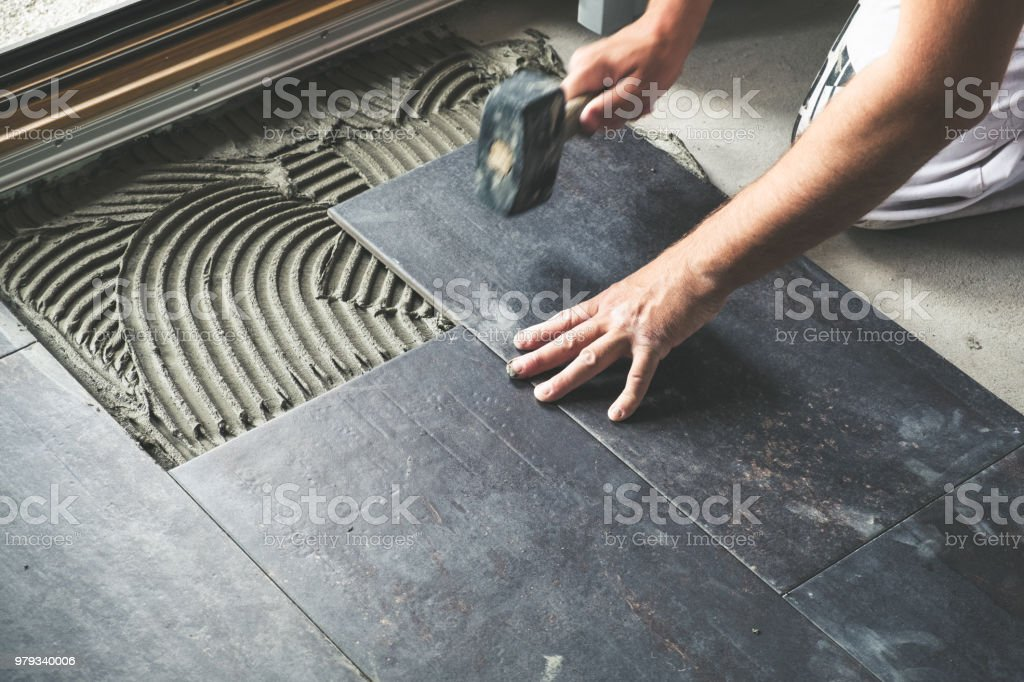 Worker placing ceramic floor tiles royalty-free stock photo