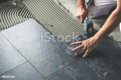 istock Worker placing ceramic floor tiles 980300364
