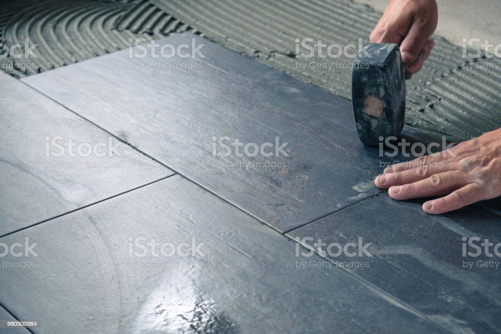 Worker placing ceramic floor tiles stock photo