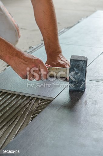 istock Worker placing ceramic floor tiles 980300426