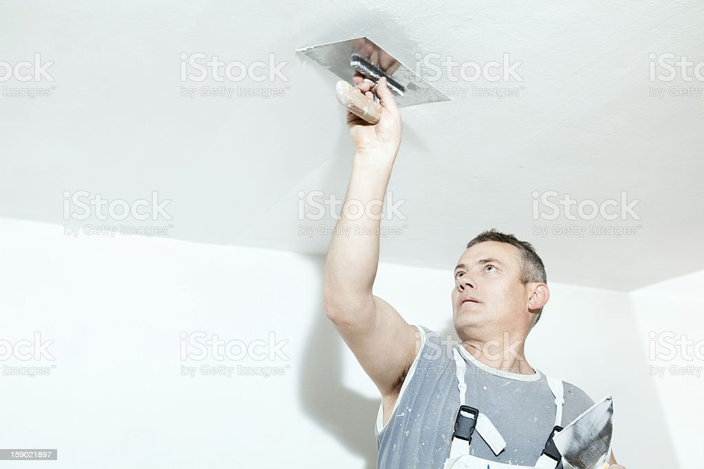 Worker plastering over a white ceiling stock photo
