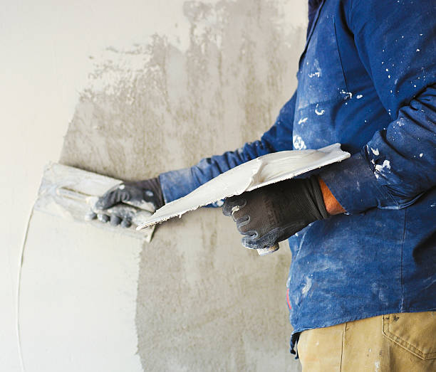 worker plastering tool plaster marble on interior plaster rough worker plastering tool plaster marble on interior plaster rough.  Selective focus plaster stock pictures, royalty-free photos & images