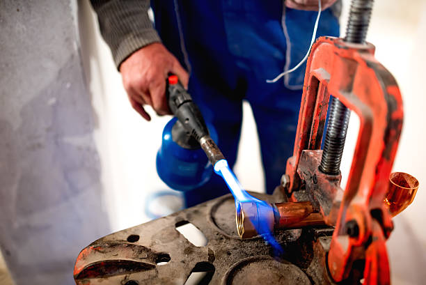 worker, plumber using blowtorch for soldering copper fittings worker, plumber using blowtorch for soldering copper fittings pipefitter stock pictures, royalty-free photos & images