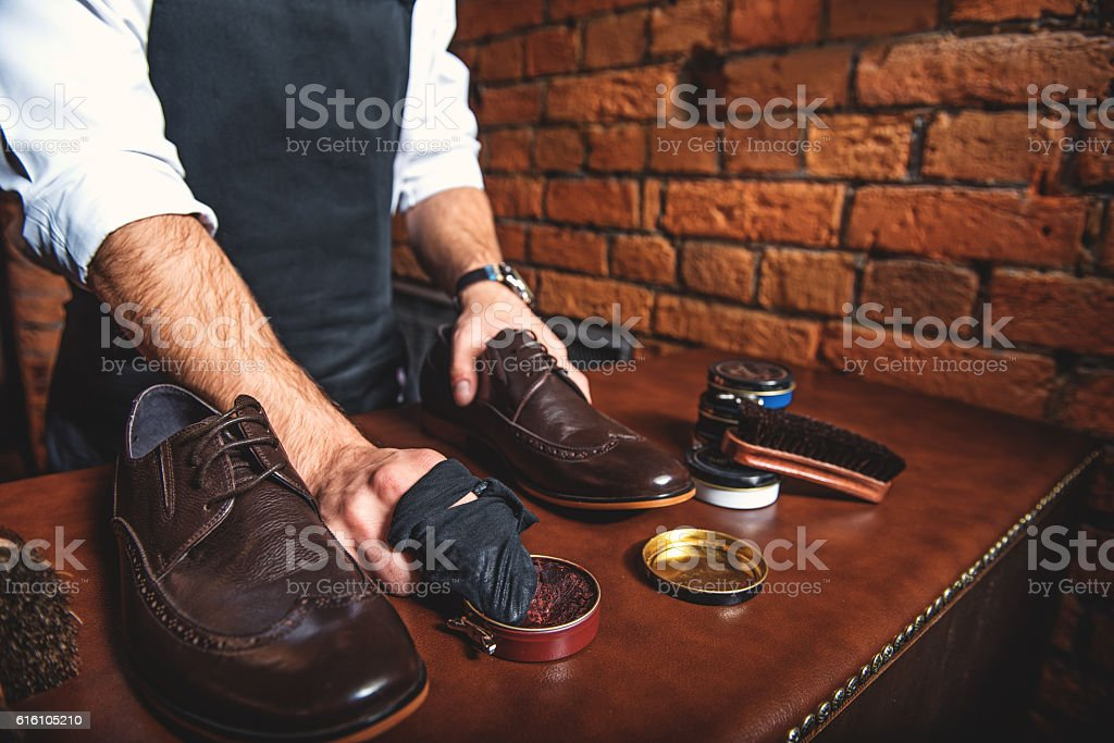 worker polishing a pair of shoes stock photo