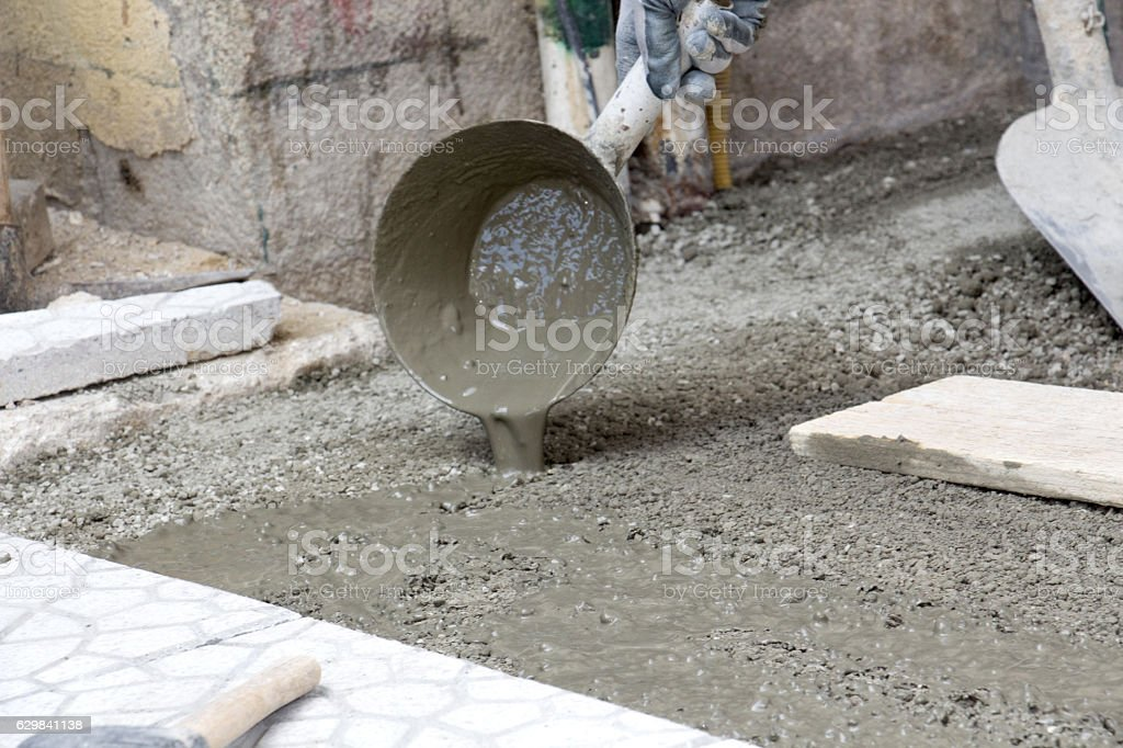 Worker pouring cement for pavement instlalation stock photo