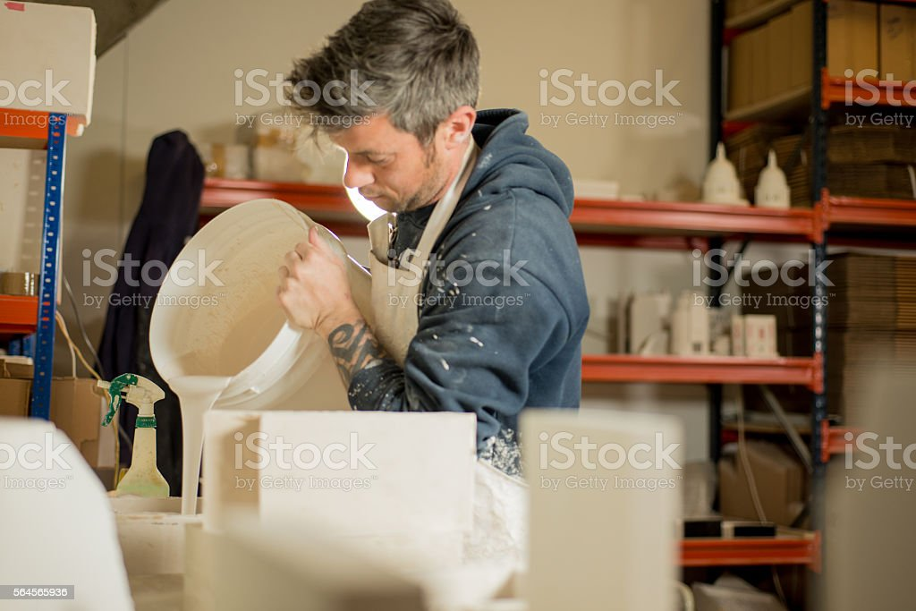 Worker Pouring Plaster onto a Mold stock photo