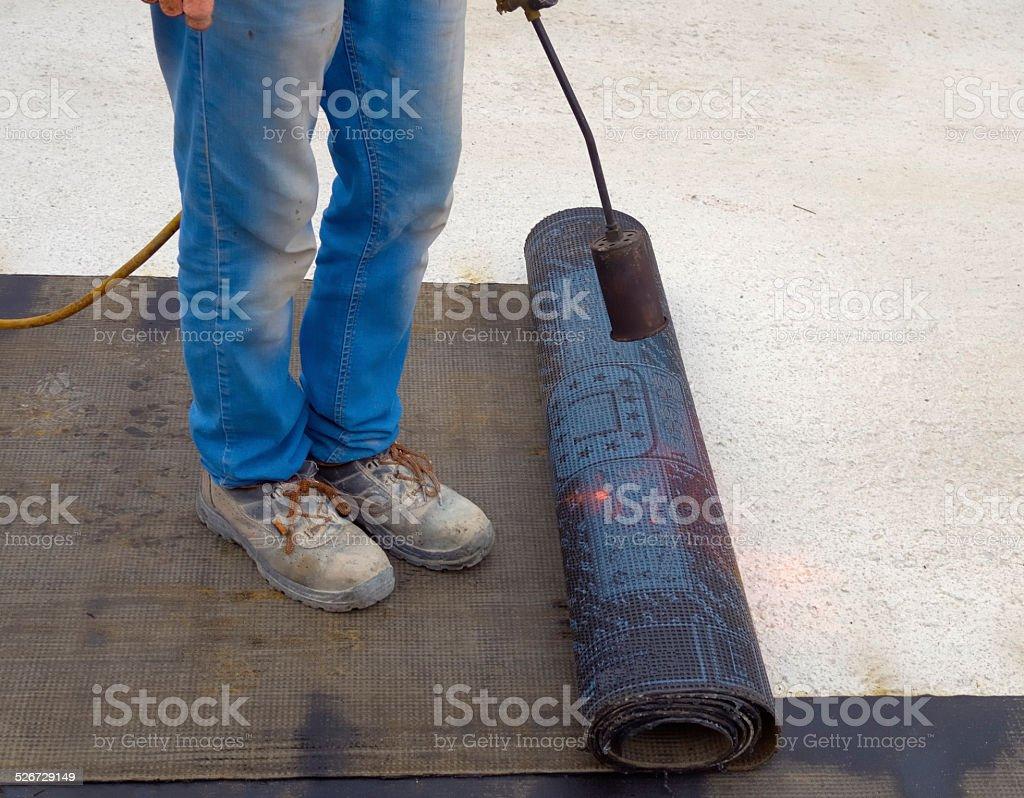 Worker preparing part of bitumen roofing felt stock photo