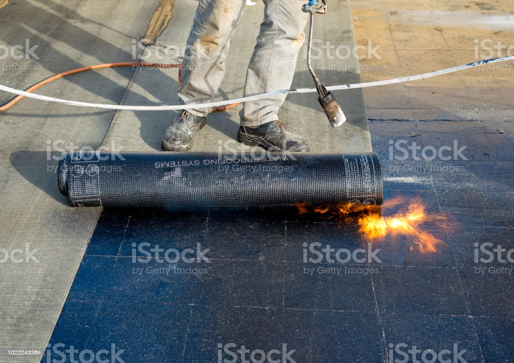 Worker preparing part of bitumen roofing felt roll for melting by gas heater torch flame. On the back of the sheath there is the stamp  'Made in Italy' product stock photo