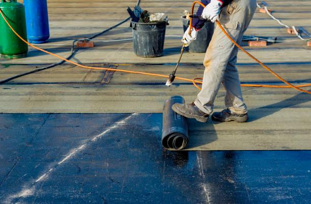 """werknemer deel van bitumen dakbedekking vilt rollen voor smelten door kachel fakkel gasvlam voorbereiden. op de achterkant van de schede is er het stempel """"made in italy"""" product - dak stockfoto's en -beelden"""