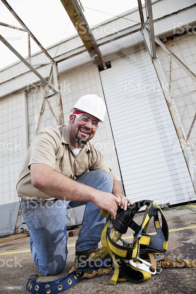 Worker preparing safety harness stock photo