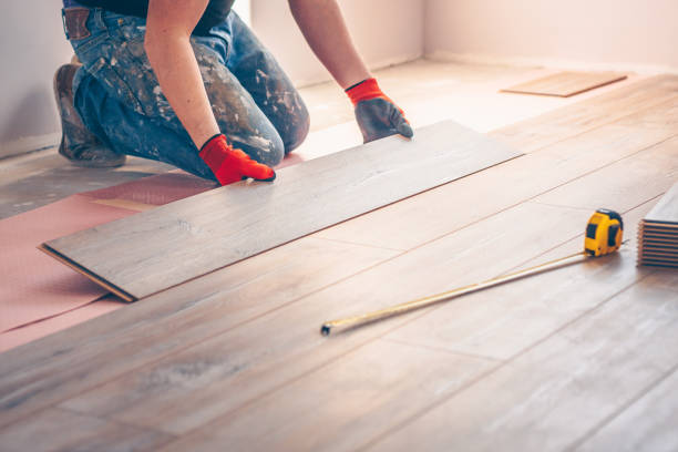 Worker professionally installs floor boards stock photo