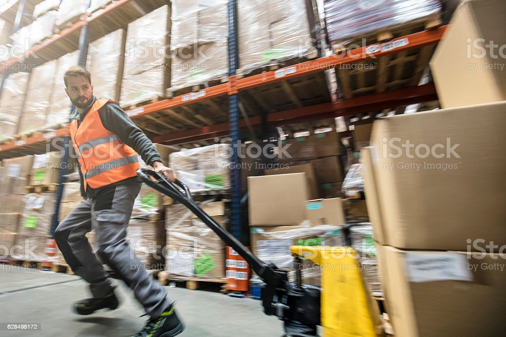Worker pulling cardboard boxes on hand truck stock photo