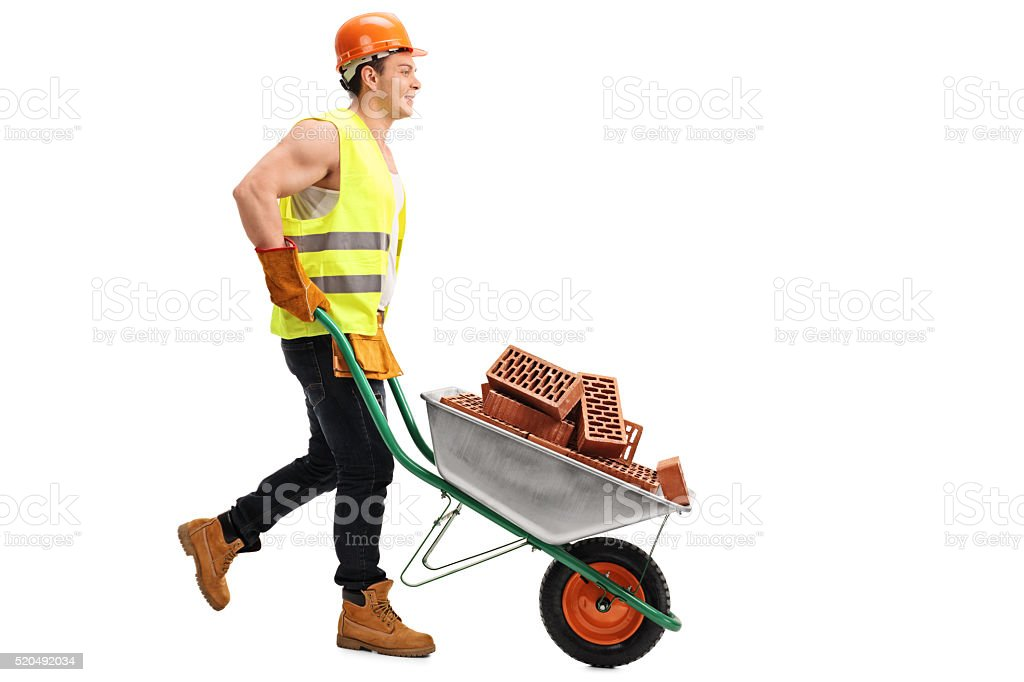 Worker pushing a wheelbarrow full of bricks stock photo