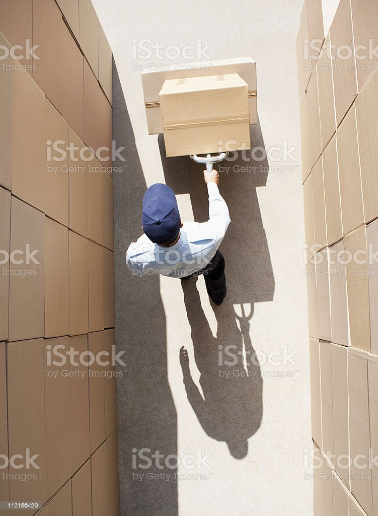 Worker pushing boxes on hand truck stock photo
