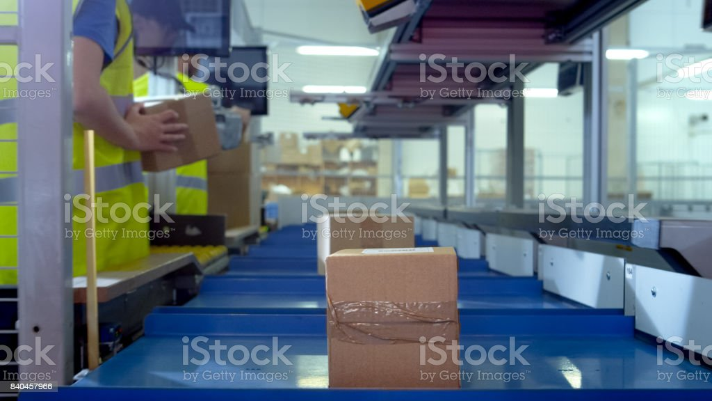 Worker Puts Parcel From Moving Belt Conveyor at Post Sorting Office. Box POV. stock photo