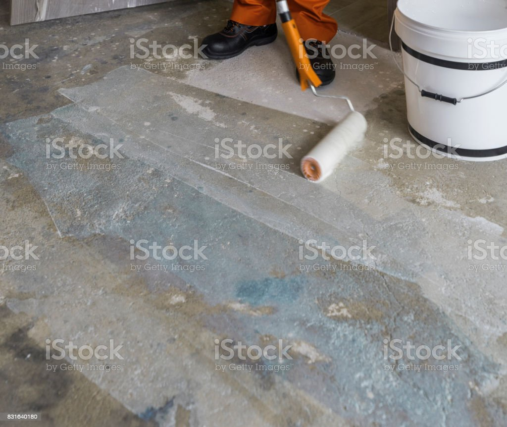 Worker puts primer with roller on concrete floor. House under construction stock photo