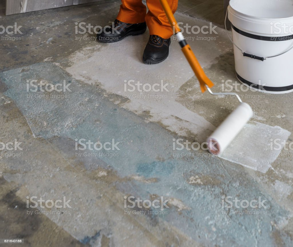 Worker puts primer with roller on concrete floor in room from unfinished apartment stock photo