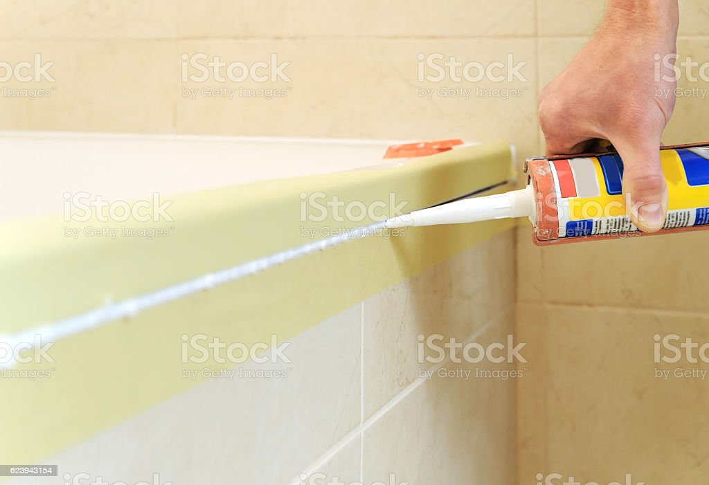 Worker puts silicone sealant. stock photo