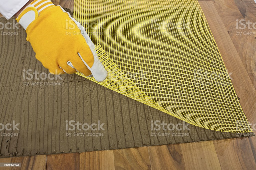 worker puts the reinforced  fiber mesh on old wooden floor royalty-free stock photo