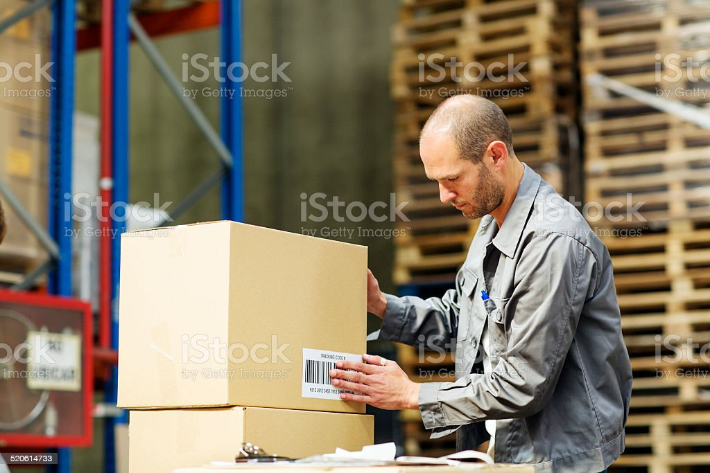 Worker putting barcode on box in warehouse stock photo
