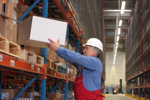 Worker Putting Box On Shelf In Warehouse Stock Photo - Download Image Now