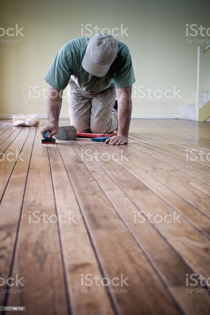 Worker putting finishing details on hardwood flooring stock photo